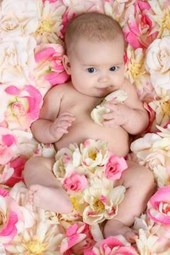 Baby in a Bed of Pink and White Flowers