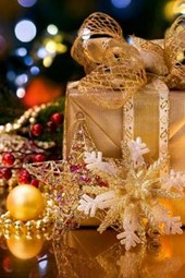 A Gold Paper Wrapped Present in Front of the Christmas Tree