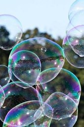 Blowing Soap Bubbles Highlighted Against Green Trees and a Blue Sky Journal